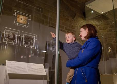 A woman and young child looking at objects in Open Treasure