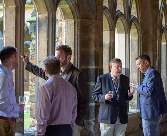 A group of business people talk in the Cloister