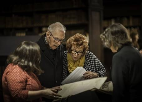 A group examining a Durham Cathedral library book