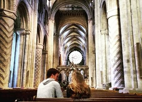 Two people sitting in pews inside Durham Cathedral