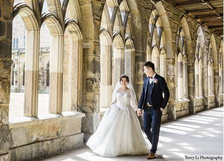 A couple in wedding clothes in the cloisters of Durham Cathedral